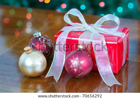 Christmas present in red and gold with ornaments - stock photo