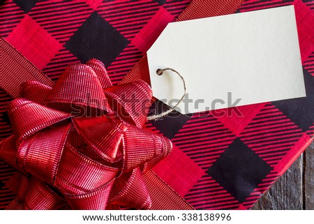 Christmas present wrapped in red and black plaid wrapping paper with red bow and blank tag sitting on wooden table - stock photo