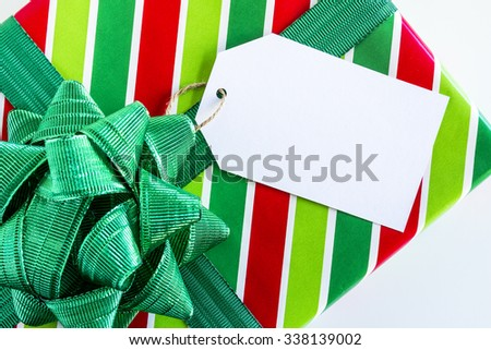 Christmas present wrapped in red and green striped wrapping paper with shiny green bow and blank tag sitting on white background - stock photo