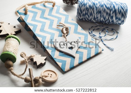 Christmas present wrapping background. Chevron bag, wooden heart, pinecones. Modern lifestyle composition in scandinavian style