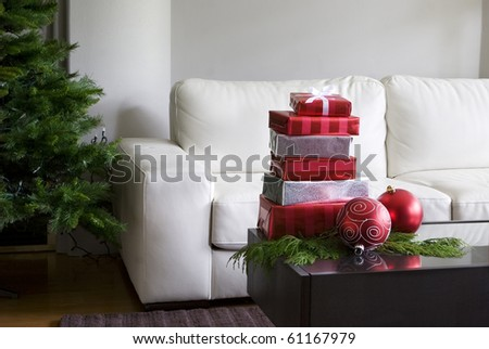 christmas presents and red ornaments on coffee table with xmas tree - stock photo
