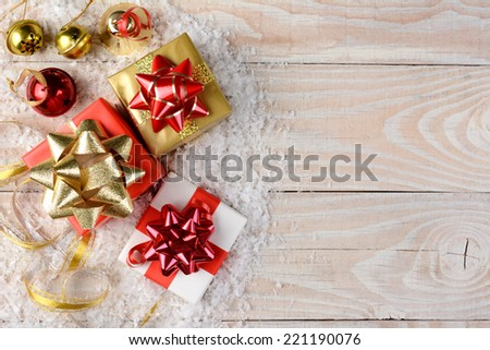 Christmas presents, bells and ribbon with artificial snow on a rustic wooden table. Horizontal format with copy space. - stock photo