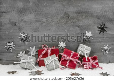 Christmas presents in red and silver on wooden grey background. - stock photo