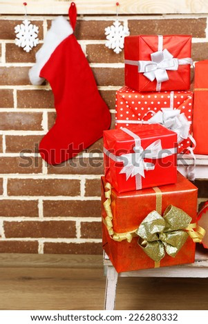 Christmas presents on stand ladder on brown brick wall background