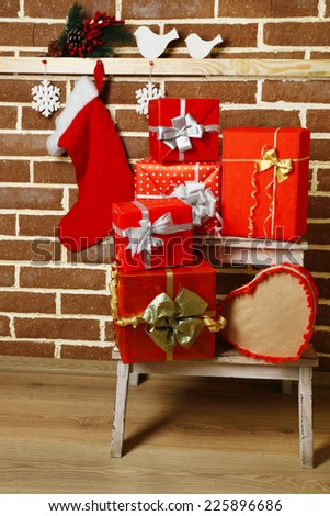 Christmas presents on white chair on brown brick wall background