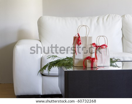 christmas presents with red bows on coffee table in modern living room - stock photo