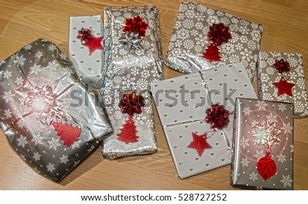 Christmas presents wrapped in seasonal paper with labels, with glowing lens flare