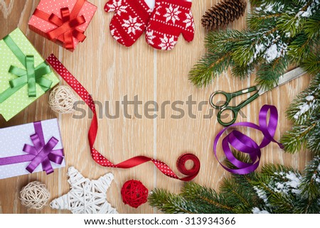 Christmas presents wrapping and snow fir tree over wooden table background with copy space