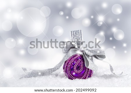 Christmas purple ball and silver ribbon. - stock photo