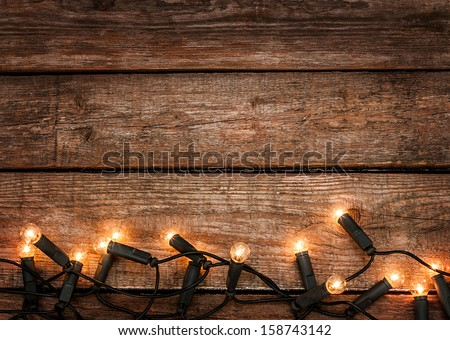Christmas rustic background - vintage planked wood with lights and free text space - stock photo
