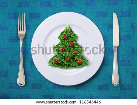 Christmas salad on white plate with knife and fork - stock photo