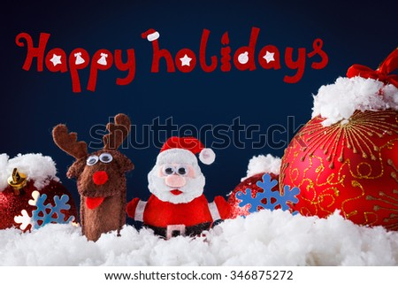 Christmas Santa and reindeer toys on snow with festive New Year balls on a blue background - stock photo