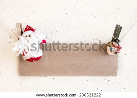 Christmas Santa Claus and snowman clothespin hanging on clothesline or rope and holding blank craft paper card on plaster background - stock photo