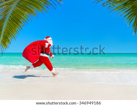 Christmas Santa Claus running at ocean tropical sandy palm beach with large sack full of presents hurry on give it for children  - New Year vacation and travel agencies price concept discounts  - stock photo