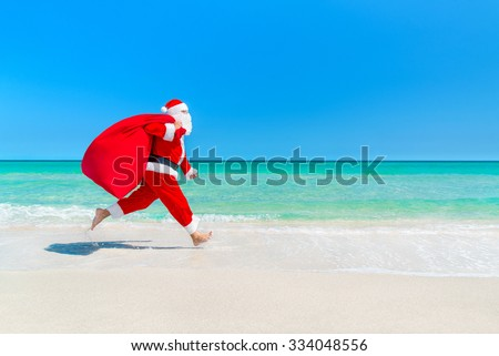 Christmas Santa Claus running with big sack full of gifts hurry on present for children along ocean tropical sandy beach - xmas travel vacation discounts and travel agencies price reductions concept - stock photo