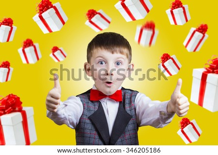 Christmas Santa -Little boy with thumb up gesture isolated over white background with falling gifts around him.Portrait of confident happy little boy showing thumbs up gesture wearing costume  - stock photo