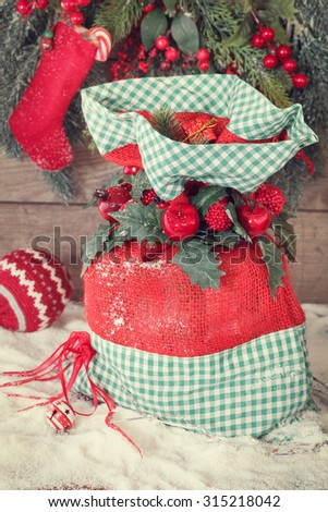 Christmas Santa sack with presents. Christmas gift sack tied  with ribbon, berries and holly leaves. Macro, selective focus Done with vintage retro filter  - stock photo