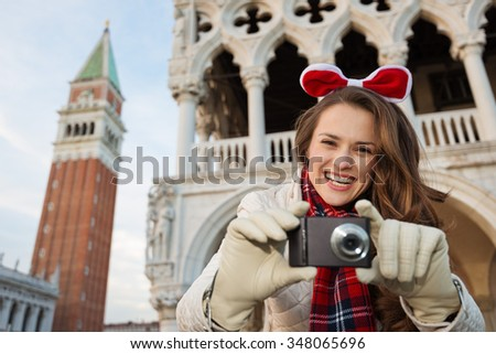 Christmas season brings spirit of travel. Portraits of smiling young woman tourist with digital photo camera. She is spending Christmas holidays in Venice, Italy - the unique city of water - stock photo