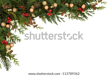 Christmas seasonal  border of holly, ivy, mistletoe, cedar leaf sprigs with pine cones and gold baubles over white background. - stock photo