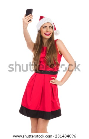 Christmas selfie. Beautiful young woman in red santa's hat and dress taking a selfie. Three quarter length studio shot isolated on white. - stock photo