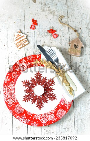 Christmas serving with red snowflake ornament plate, sparkling snowflake decor and tea-candle, with white napkin and cutlery wrapped in it an other christmas decorations - stock photo