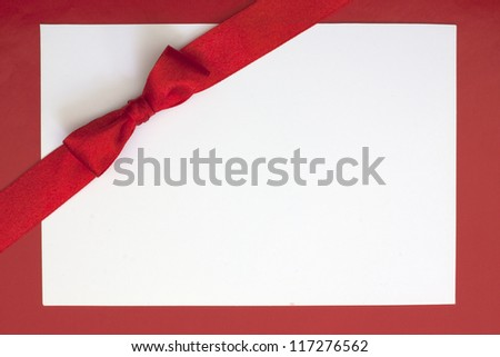 Christmas sheet of paper and red ribbon gift background - stock photo