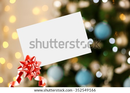 Christmas Sheet Of Paper With Bow And Ribbon On Defocused background Living room with christmas tree - stock photo