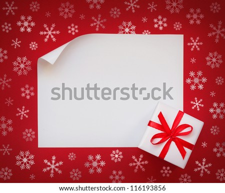 Christmas sheet of paper with cute gift box on red snowflakes background - stock photo