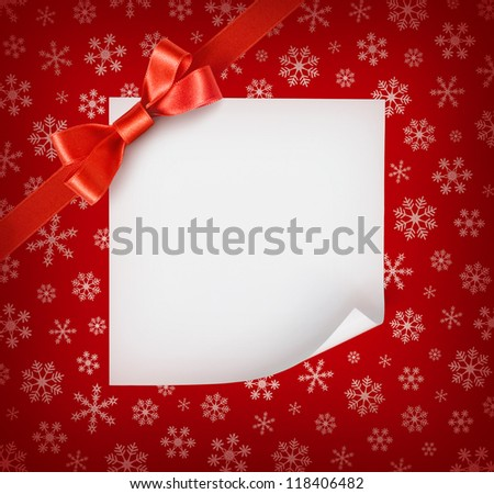 Christmas sheet of paper with red ribbon bow on red snowflakes background - stock photo