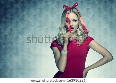 christmas shoot of beauty blonde elegant woman with red fashion dress and bright bracelet posing with funny bow on her head like a present  - stock photo