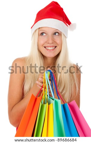 Christmas shopping woman, Happy excited santa girl in red hat and dress, holding colorful bag, looking up to empty copy space, isolated on white background - stock photo