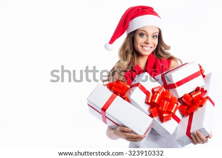 Christmas shopping woman holding many Christmas gifts in her arms wearing santa hat. Beautiful young female model isolated on white background. - stock photo