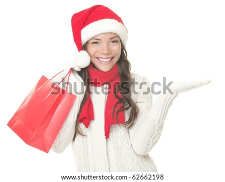 Christmas shopping woman presenting copy space. Excited santa girl showing your product or text looking sideways on copyspace with open hand palm. Asian Caucasian model isolated on white background. - stock photo