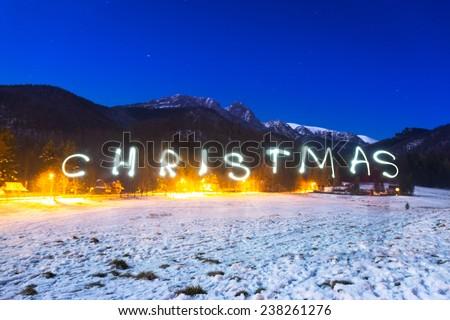 Christmas sign under Tatra mountains at night, Poland - stock photo