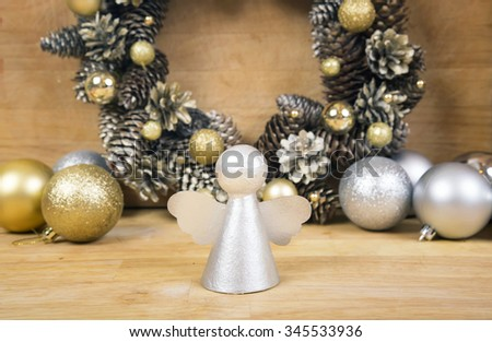Christmas silver angel on wooden surface with wreath of cones and gold balls on background. - stock photo