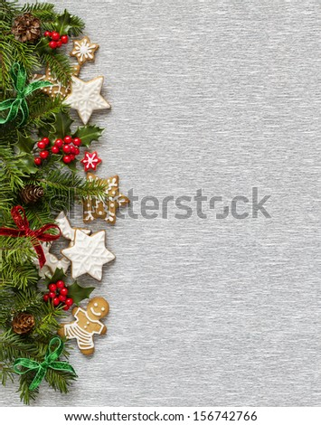 Christmas Silver background with holly branch, berries, firtree and ginger cookies. - stock photo