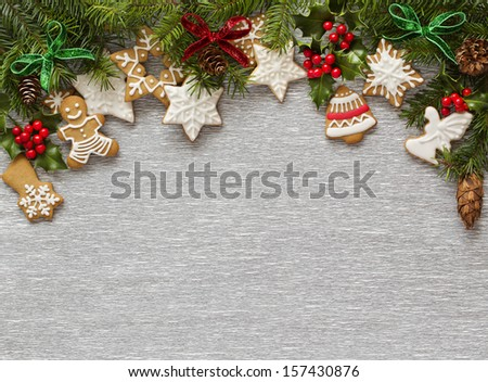 Christmas Silver background with holly branch, berries, firtree and gingerbread cookies. - stock photo