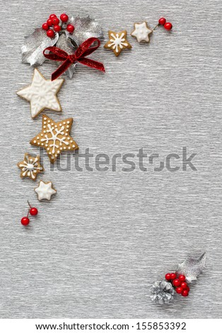 Christmas Silver background with holly branch, berry and ginger cookies. Vertical Border - stock photo