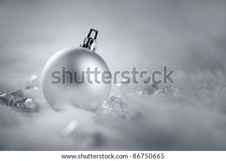 christmas silver bauble on fur snow and ice cold winter - stock photo