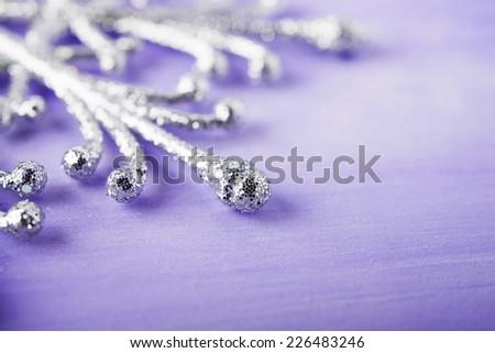 Christmas silver snowflake on purple wood background.  - stock photo