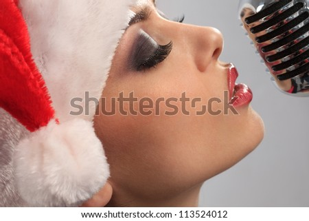 Christmas Singer standing in front of a microphone. Isolated on a grey background - stock photo