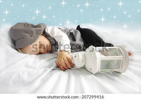 Christmas sleeping newborn baby with lantern in suit and hat on starry blue background. Photo for calendar, card  etc. Christmas concept. - stock photo