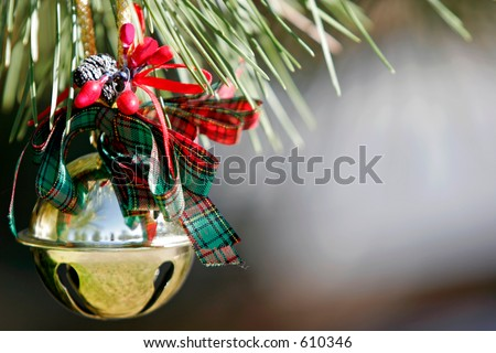 Christmas Sleigh Bell Ornament on a Pine tree - stock photo