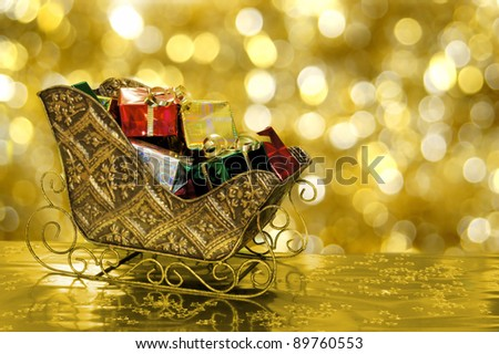 Christmas sleigh or sled filled with gift boxes with gold background - stock photo