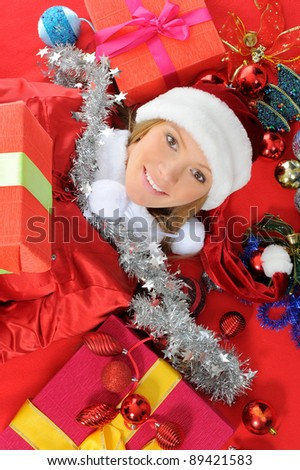 Christmas smiling woman in red santa cap with a gift.