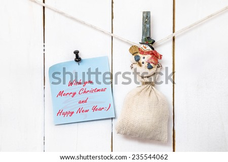 Christmas snowman clothespin hanging on clothesline or rope and holding sack and blue Christmas greeting note paper with push black pin on wood background - stock photo