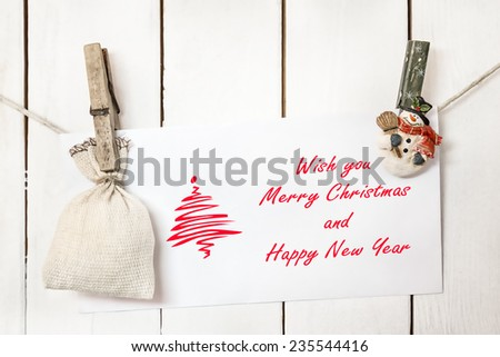 Christmas snowman clothespins hanging on clothesline or rope and holding Christmas greeting card and sack on wood background - stock photo