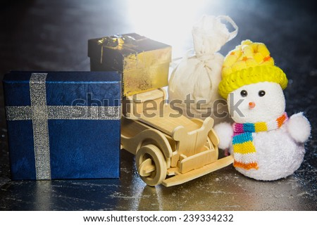 Christmas snowman toy and old vintage wooden automobile with golden or yellow and blue gift boxes and sack on silver or metal grunge surface with backlight from behind - stock photo