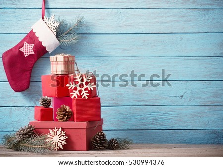 Christmas sock with gifts on  wooden wall