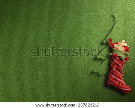 Christmas sock with red gift box on green paper background - stock photo